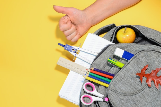 Рука и рюкзак со школьными принадлежностями