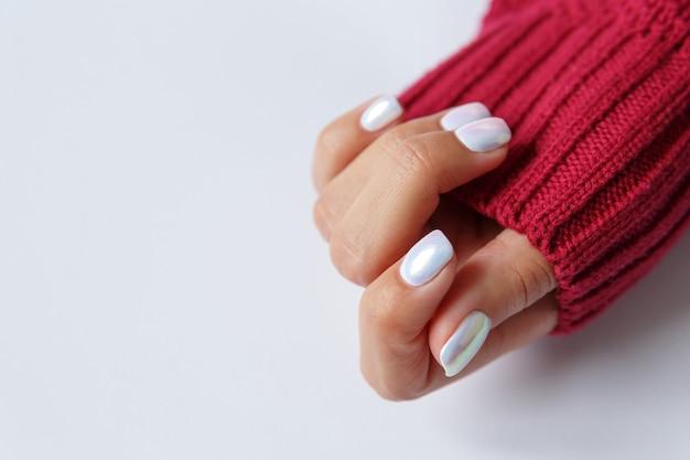 Рука и красивый жемчужный маникюр крупным планом