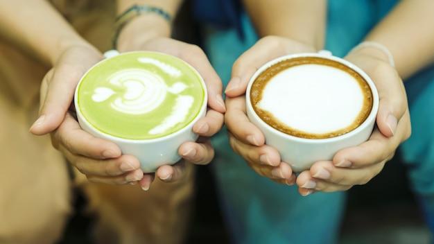 手とコーヒーと熱い緑茶若者は熱い飲み物を飲むのが大好きです。