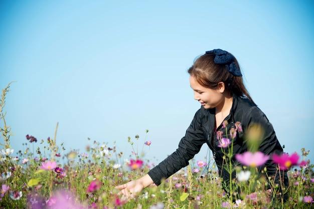 太陽の光とフラワーガーデンの手とコスモスの花