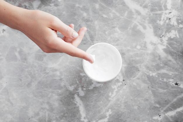 手とクリームの背景のトップビュー