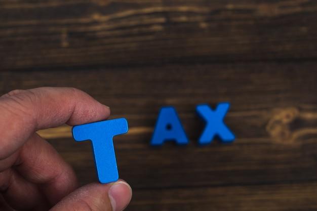 手と指が木の上の税単語のテキスト文字を配置します。