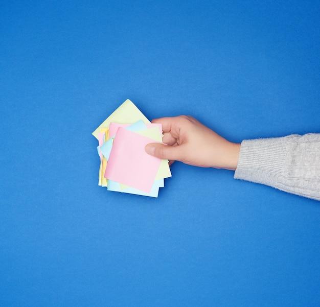 Рука и много пустых бумажных разноцветных наклеек на синей поверхности