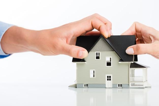 Рука и модель дома развод разделение дома недвижимость человеческая рука жилая структура