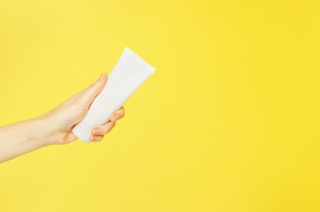 黄色の背景の分離の女性の手の白いプラスチック容器に手とネイルクリーム。ボディケアローション。シンプルな空のパッケージ美容化粧品。モックアップ、スペースをコピーします。