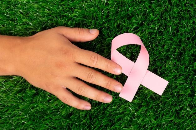 手と緑の芝生にピンクのリボン、がんとの闘いで希望。