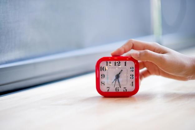 毎朝アラームを表示する手と赤の目覚まし時計