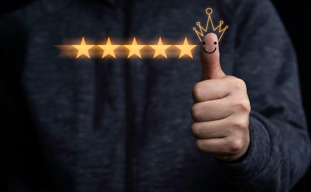 手と親指は黒い背景に5つの黄色い星で立ち上がり、最高の顧客満足度と高品質の製品とサービスの評価を提供します。