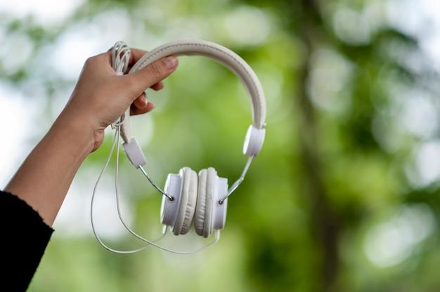 Ручные и белые наушники, устройства для ежедневного прослушивания музыки музыка и музыкальные концепции