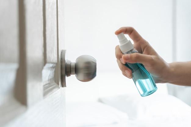 Ручное нанесение спиртового спрея на дверь, дверную ручку спальни для защиты от коронавируса.