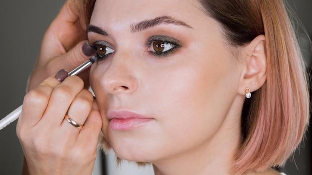 Hand applying eye shadow on lady