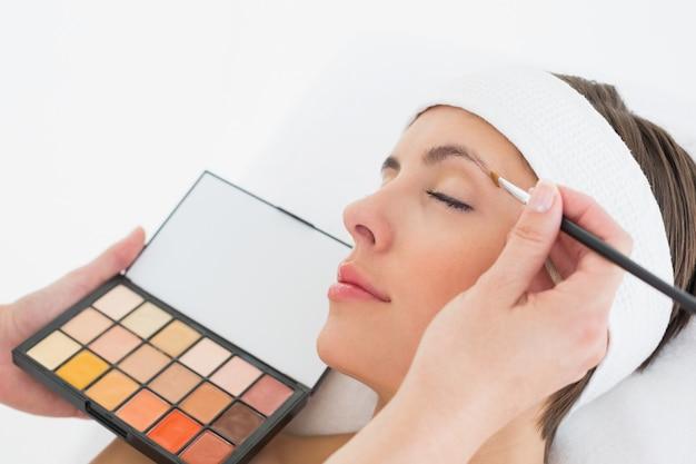 Hand applying eyeshadow to beautiful woman