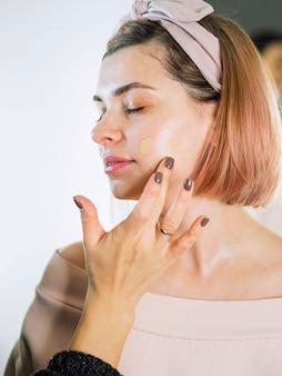 Hand applying foundation on woman