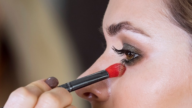Hand applying make up on model