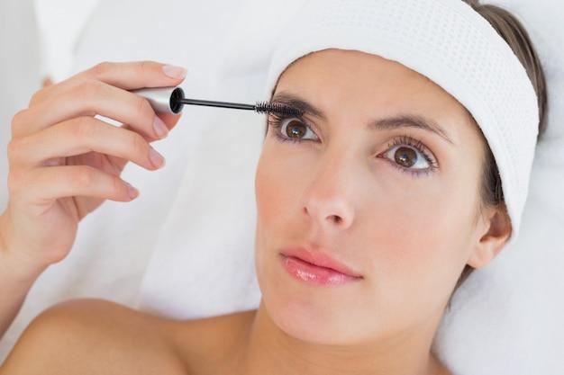 Hand applying mascara to beautiful woman