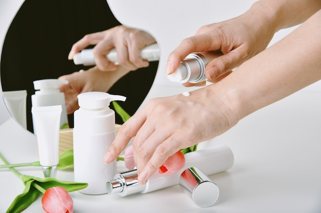 Hand applying natural skincare, cosmetic bottle containers packaging with tulip flower essence, organic beauty product concept.