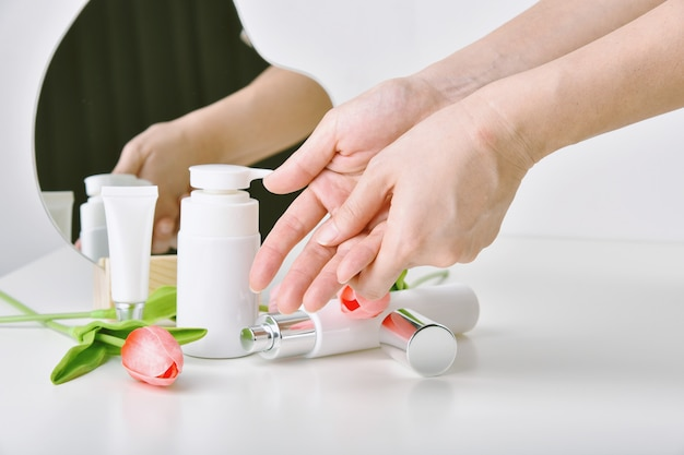 Hand applying natural skincare with tulip flower essence