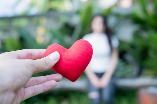 バレンタインの愛を置き換えるために、手は夕方に赤いハートを持っています。