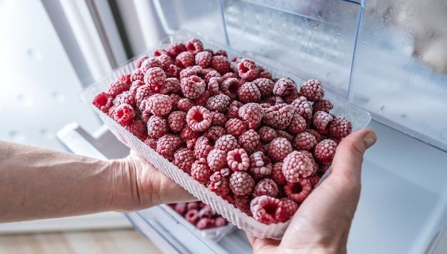 手は冷蔵庫の冷凍庫から冷凍ラズベリーの容器を取っています