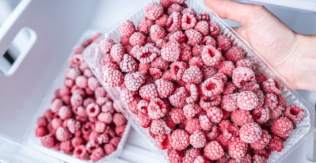 Hand are taking a container of frozen raspberries out of the freezer of the fridge
