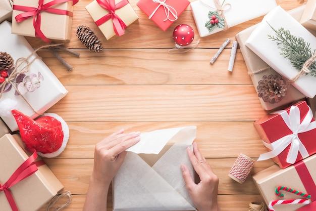손은 축하를 위해 메리 크리스마스와 새해 복 많이 받으세요 장식의 선물을 포장하고 있습니다