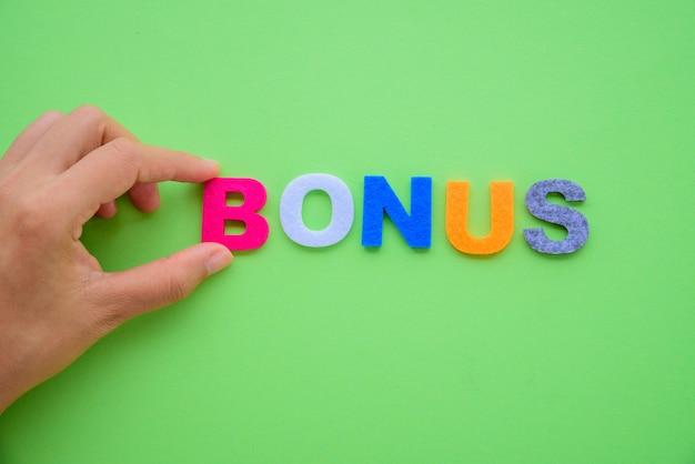 Hand arrange bonus alphabets word on green background.