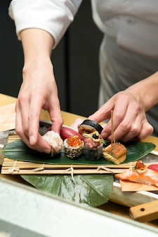 Hand arrange sushi for serving
