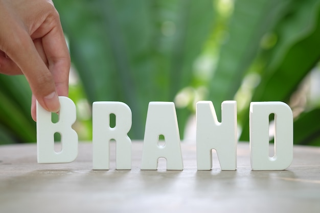 Hand arrange white letters brand