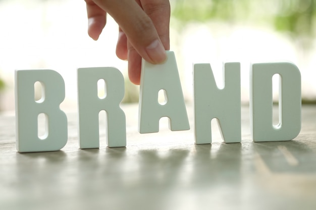 Рука устроит белые буквы brand