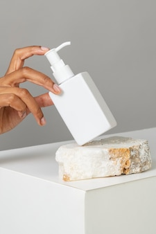 Hand arranging a blank white pump bottle on a stone