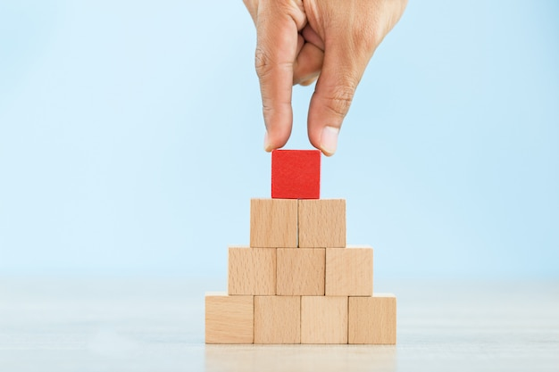 Hand arranging red wood block stacking as step stair,with the concept of a thriving business going for success.