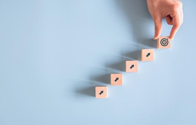 Hand arranging wood block stacking as goal success