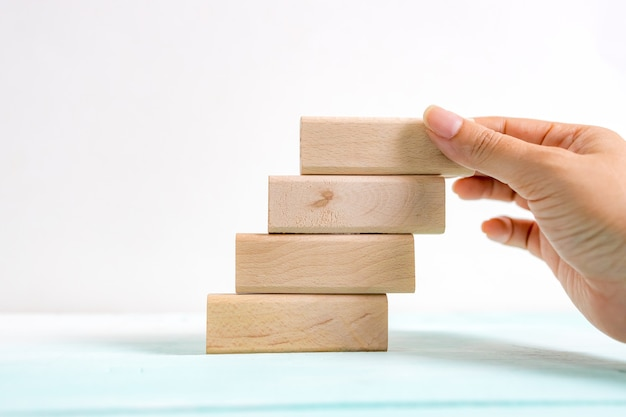 Hand arranging wood block stacking as step stair. business concept for growth success process. stairs up as a symbol of career growth up or business success.