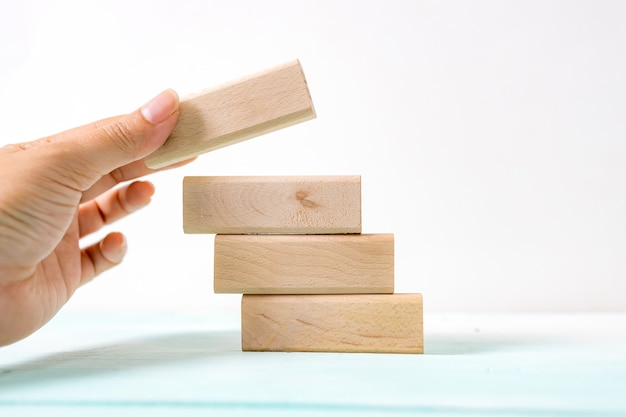 Hand arranging wood block stacking as step stair. business concept for growth success process. stairs up as a symbol of career growth up or business success. Premium Photo
