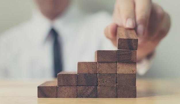 Ручная сборка деревянных блоков в качестве ступеньки. концепция карьерной лестницы для успешного роста бизнеса, копирование пространства