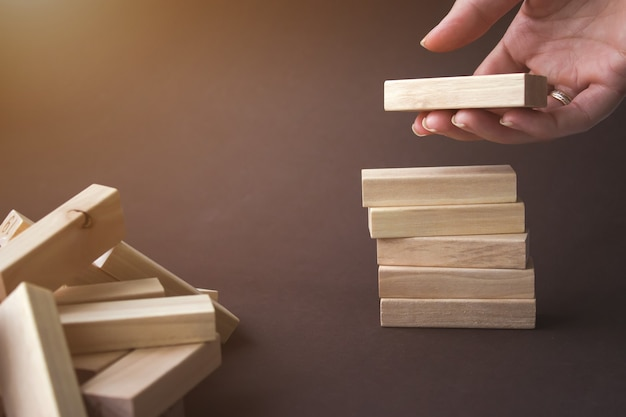 Hand arranging wood block stacking as step stair. planning and strategy in business.alternative