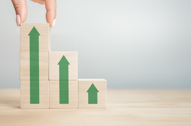 Hand arranging wood block stacking as step stair with green arrow up. cropped hands of person stacking wooden blocks on table. ladder career path for business growth success process concept.