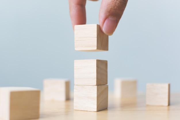 木製のテーブルの上に積み上げ木製ブロックを手します。