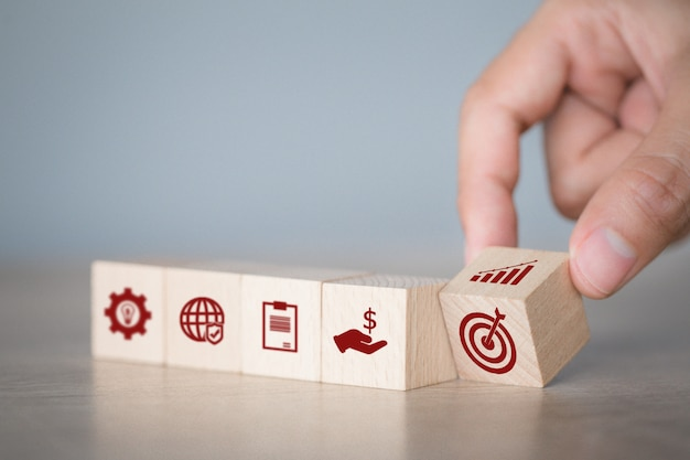 Hand arranging wood block stacking with icon arrow and business,targeting the business concept.