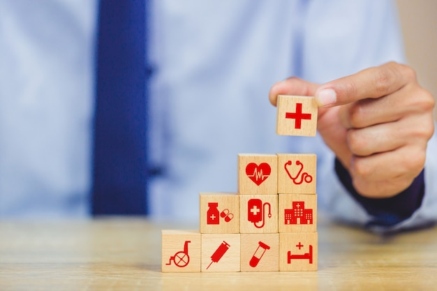 Hand arranging wood block stacking with icon healthcare medical.