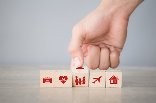 Hand arranging wood block stacking with icon insurance: car,