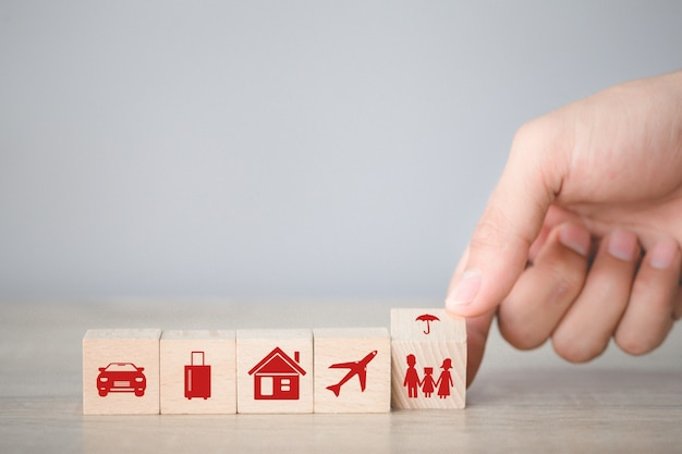 アイコン保険で積み重ねて積み木ブロックを配置する手:車、