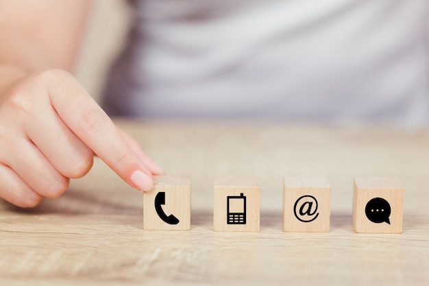 Hand arranging wood block stacking with iconl telephone, mail, address and mobile phone