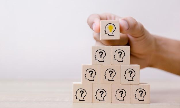 아이콘 머리 인간의 기호 및 전구, 개념 창조적 인 아이디어와 혁신 나무 블록을 배열하는 손.
