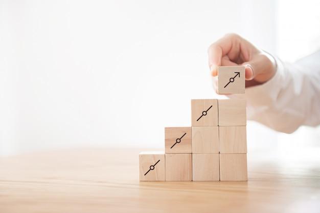 アイコンの成長とステップ階段として木製キューブスタッキングを配置する手。