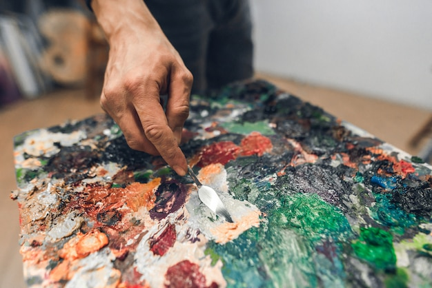 Hand of the artist's man from the palette knife mixes the paint on the palette