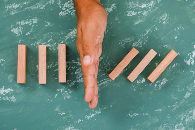 Hand as barrier dividing wooden blocks.