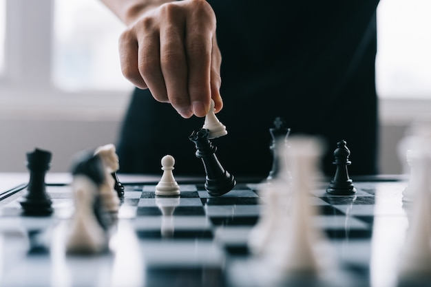 Hand of asian businessman moving chess figure in competition success play