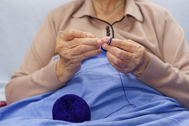 Hand of asian senior or elderly old lady woman crochet dark blue yarn. hobby and handicraft concept.