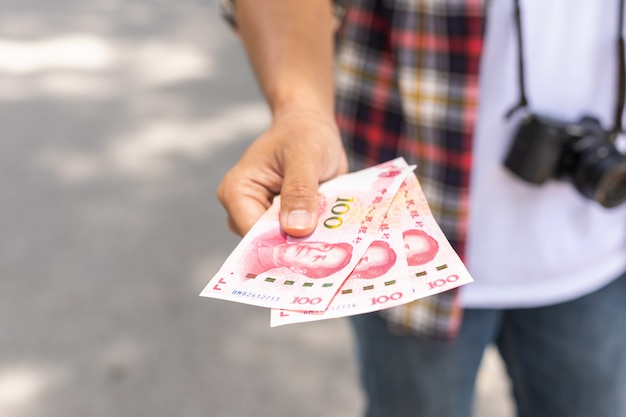 Hand of asian tourist giving banknote and black wallet that he found in tourist attraction.